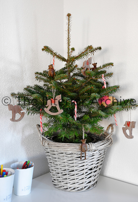A little Christmas tree for a little child, decorated with traditional sweets and rocking horse ornaments