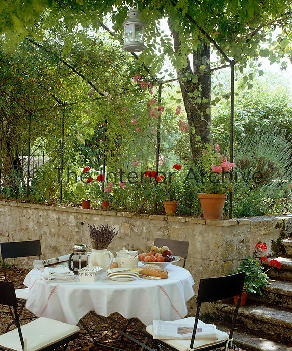 Next to the mellow stones of an old garden wall and under the shade of a pergola a table is laid for breakfast