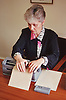 Woman with visual impairment sitting at desk using Braille typewriter,