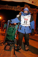 Saturday March 17, 2007  - Nome, Alaska ----  Cindy Gallea at the Nome finish line with her sled that has two broken runners.  One completley broke off just 40 miles from the finish line and the other cracked 10 miles from Nome and is barely hanging on.