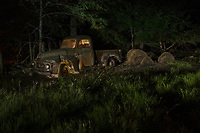 An abandoned old pickup photographed at night with light painting.