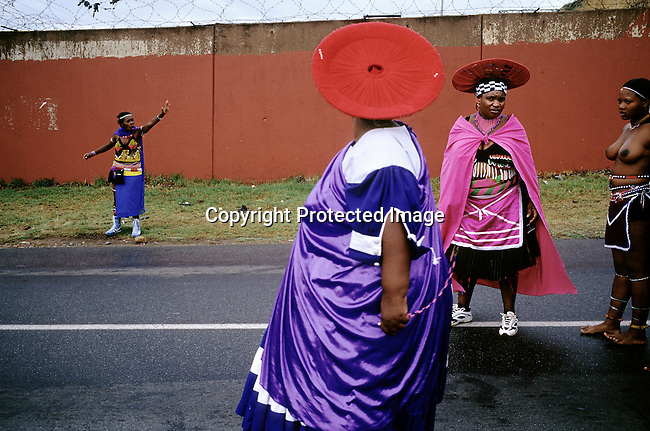 Zulu women dressed in traditional clothing stop the traffic as they are marching with about fifty virgins that celebrate their virginity on March 11, 2005 in Soweto, Johannesburg, South Africa. The girls were earlier checked if they were virgins or not. Soweto is the biggest township in South Africa, and has a population of about 3.5 million. (Photo by: Per-Anders Pettersson)