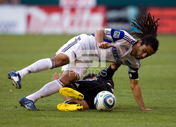 Christian Castillo (12) of D.C. United tries to tackle the ball away from Stephane Auvray (8) of the Kansas City Wizards at RFK Stadium in Washington, DC.  D.C. United defeated the Kansas City Wizards, 2-1.