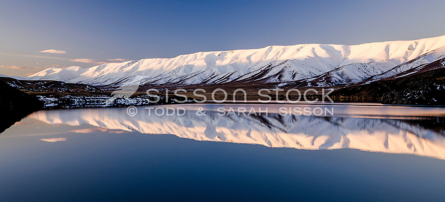 Serene reflection of snow covered Hawkdun Range in Falls Dam, near St Bathans, Central Otago, South Island, New Zealand - stock photo, canvas, fine art print