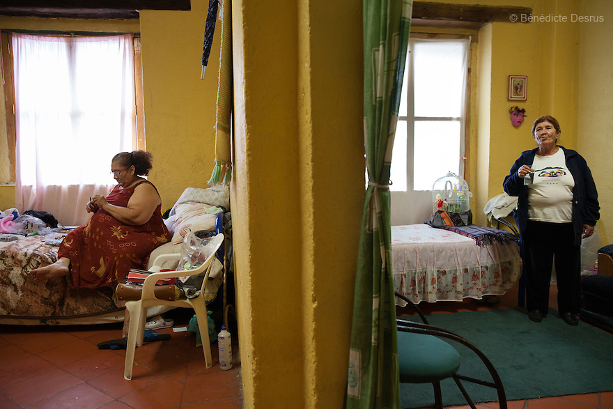 María Isabel and Gloria, both residents of Casa Xochiquetzal, in their respective bedroom at the shelter in Mexico City, Mexico on July 8, 2013. Living under a single roof hasn't been easy. Although many of the women knew one another for years on the streets, they competed for clients. Casa Xochiquetzal is a shelter for elderly sex workers in Mexico City. It gives the women refuge, food, health services, a space to learn about their human rights and courses to help them rediscover their self-confidence and deal with traumatic aspects of their lives. Casa Xochiquetzal provides a space to age with dignity for a group of vulnerable women who are often invisible to society at large. It is the only such shelter existing in Latin America. Photo by Bénédicte Desrus