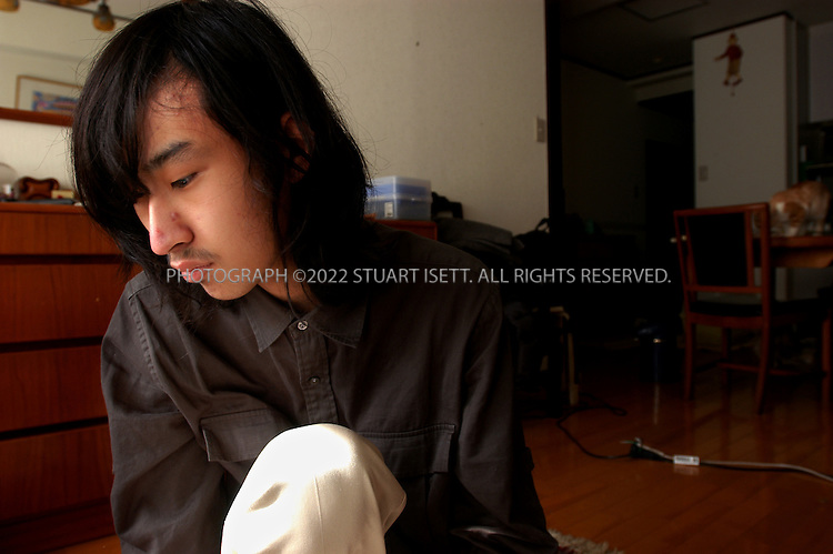 11/29/2002--Tokyo, Japan..19 year old Dai Hasebe at his parents home in Meguro Ward Tokyo, plays with one of the two cats given to him by his parents. Dai has been a 'hikikomori', or shut-in, since he was 11, rarely venturing out of his family's apartment, instead spending all his time shut off from the world in the tiny apartment. ..Experts estimate that at up to a million Japanese live as shut-ins as they hide from the social pressures of Japanese society.....All photographs ©2003 Stuart Isett.All rights reserved.This image may not be reproduced without expressed written permission from Stuart Isett.