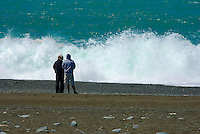 Two people watch as big turquoise waves crash on beach