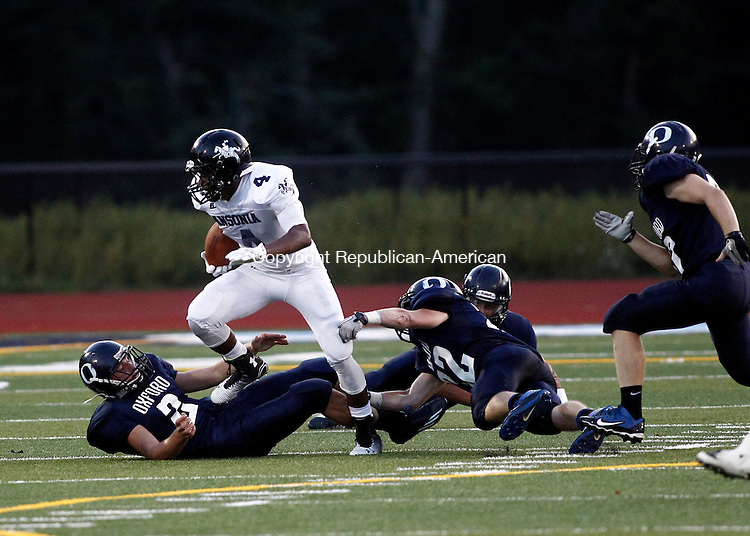 Oxford, CT- 01 September 2014-081114CM08-  Ansonia's Tajik Bagley breaks a tackle from Oxford's #2 Joseph Romagna and #22 Gunnar Fay during their matchup in Oxford on Thursday.    Christopher Massa Republican-American