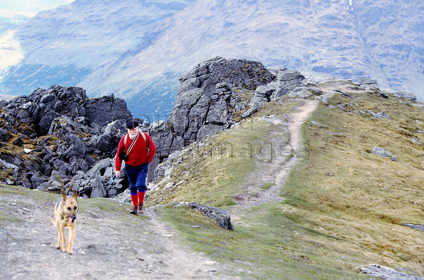 Man walking with is dog along a mountain path