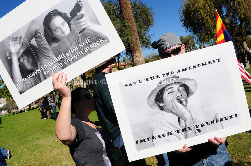 "Phoenix, Arizona. January 19, 2013 - A couple of demonstrators who participated in Saturday's rally to oppose proposed changes to existing US gun laws hold signs. One of the signs shows a picture of president Obama that reads: ""Save the 2nd Amendment, impeach the president."" As President Barack Obama proposed new gun regulations last week, gun owners demonstrated against it with national ""Guns Across America"" rallies to defend the Second Amendment. Dozens showed up at the Arizona State Capitol, many of them carrying weapons. Photo by Eduardo Barraza © 2013"