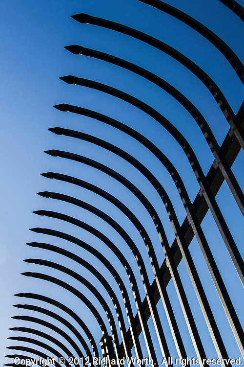 The top of a public park fence, its metal slates curve outward and each come to a point with a clear blue sky background.