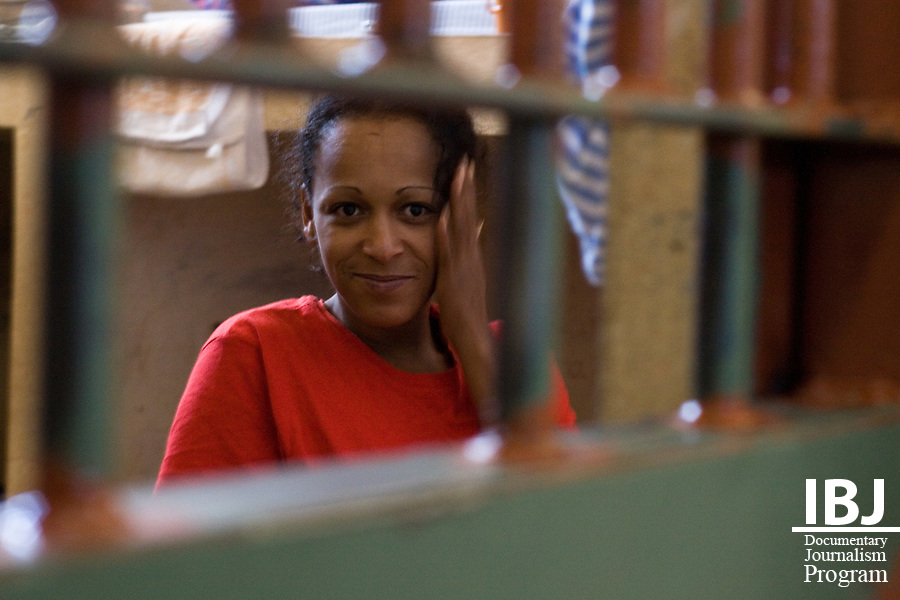 A woman smiles at the camera in Floramar Prison located in Divinopolis, Brazil. 27 inmates are included amongst 273 male prisoners in a facility that is twice over capacity. IBJ Fellow Dr. Saliba is educating prison communities of their rights to habeas corpus protecting the accused from illegal internment
