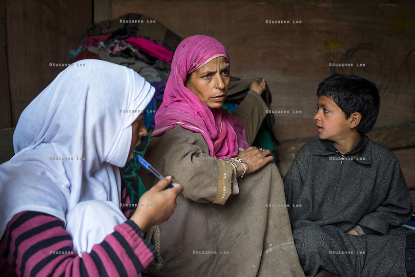 (Alison Griffin to fill in names) (mother's name) holds a blanket, the only thing she managed to grab as she and her children fled their house during the floods in Abikarpora village on the Dal Lake, Srinagar, Jammu and Kashmir, India, on 25th March 2015. Since the flood, she has been widowed, and is left with four young children and no home. Her family now lives in a temporary shelter built using the emergency shelter kit, and continues their recovery with the help of relief kits such as education kit, food basket, hygiene kit and non-food items from Save the Children. Photo by Suzanne Lee for Save the Children