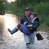 BORKI, POLAND, MAY 24, 2010:.Rescue worker evacuating villager Halina Waszkiewiczowa..The latest chapter of disastrous floods in Poland has been opened yesterday, May 23, 2010, after Vistula river broke its banks and flooded over 25 villages causing evacualtion of most inhabitants..Photo by Piotr Malecki / Napo Images..BORKI, POLSKA, 24/05/2010:.Strazak niesie mieszkanke wsi Haline Waszkiewiczowa. Najnowszy akt straszliwych tegorocznych powodzi zostal rozpoczety wczoraj gdy Wisla przerwala waly na wysokosci wsi Swiniary kolo Plocka..Fot: Piotr Malecki / Napo Images ..