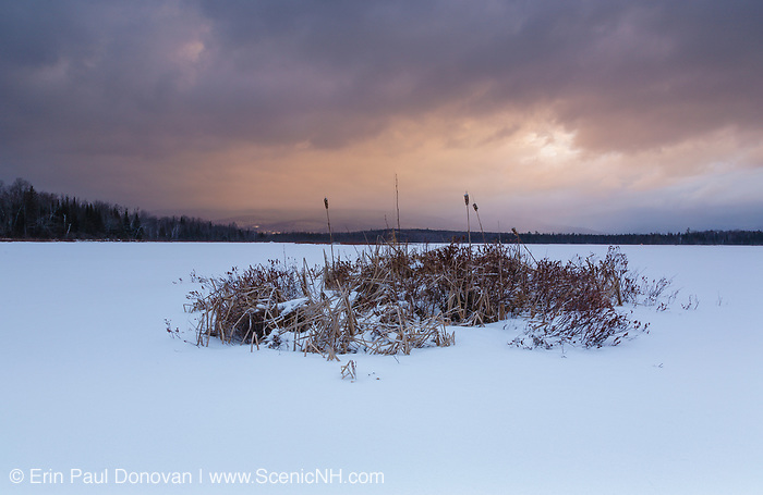 Sunrise from Cherry Pond during stormy weather in Jefferson, New Hampshire USA during the winter months. This pond is located in Pondicherry Wildlife Refuge.