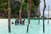 Raja Ampat Archipelago, West Papua, Indonesia, December 2010. The first poles for a stilted house of the homestay project are planted in the sand.  Thousands of small islands fringed by coral reefs and blue water mangroves litter the Raja Ampat archipelago. The turquoise and blue waters are teeming with marine life that forms the livelihood for the local Papuan population. The Raja Ampat Research & Conservation Centre (RARCC) supports the locals to develop a community based, sustainable tourism project, inviting visitors to explore their islands by sea kayak and experience the culture by staying amongst the local people in traditional style homestays. Photo by Frits Meyst/Adventure4ever.com