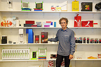 USA. California state. San Francisco. Potero Hill district. Ives Béhar stands in his offices at Fuseproject with some products he has designed. His hand holds a door handle with his designed August, a Smart Lock maker. Yves Béhar (born 1967) is a Swiss designer, renowned entrepreneur, and sustainability advocate. He is the founder and principal designer of Fuseproject, an award-winning industrial design and brand development firm. Béhar's design work emphasizes the integration of commercial products with sustainability and social good. His clients have included Herman Miller, PUMA, MINI, See Better to Learn Better, General Electric, Swarovski, Samsung, Jimmyjane, and Prada. Béhar is also Chief Creative Officer of the wearable technology company Jawbone, and Co-founder and Chief Creative Officer of August, a Smart Lock maker. He is the chief industrial designer of One Laptop per Child (OLPC's) XO laptop, signing on with the project in 2005 and has been with the team since March 2006. This collaboration has led to two additional laptop prototypes, the OLPC XOXO and OLPC XO-3. In 2012 SodaStream International teamed with Béhar to introduce Source, a new home soda machine designed with a special emphasis on sustainability. 15.12.2014 © 2014 Didier Ruef