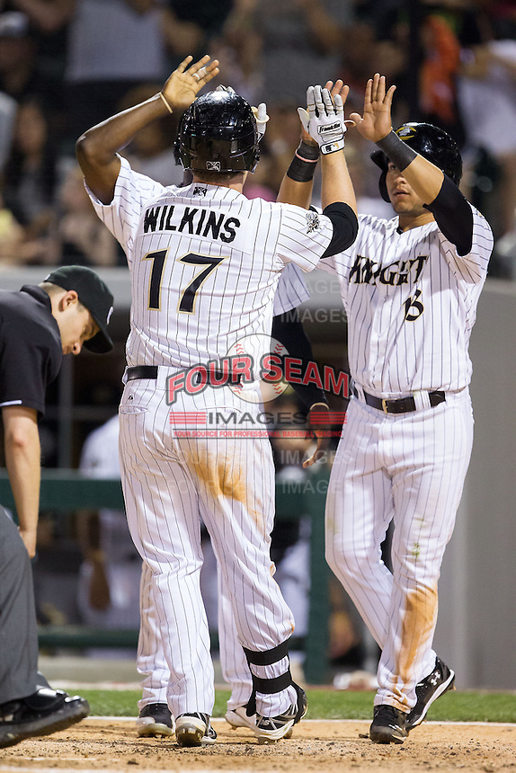 Andy Wilkins (17) of the Charlotte Knights high fives teammate Carlos Sanchez (13) after hitting a home run against the Lehigh Valley IronPigs at BB&T Ballpark on May 8, 2014 in Charlotte, North Carolina.  The IronPigs defeated the Knights 8-6.  (Brian Westerholt/Four Seam Images)