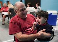 NWA Democrat-Gazette/CHARLIE KAIJO Mike Henzie of Bella Vista (left) holds Brooks Henzie, 1, as he sucks on a lollipop after getting his flu shot during a free flu vaccine clinic, Friday, October 5, 2018 at the Rogers Community Center in Rogers.<br /><br />The Benton County Health Unit of the Arkansas Department of Health (ADH) will offer free flu vaccinations at the Rogers Activity Center, 315 W. Olive, Rogers, AR., from 8:00 a.m. to 4:00 p.m. Friday. <br /><br />&Ograve;We want Benton County residents to stay healthy this flu season, and getting a yearly flu vaccination is the best line of defense,&Oacute; Loy Bailey, Benton County Health Unit Administrator, said. &Ograve;We encourage everyone to come to the mass clinic or the local health unit to get their flu shot.&Oacute;