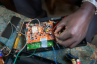 Man repairs radio in the market. Kabaya, Rwanda. (Photo by Tadej Znidarcic)