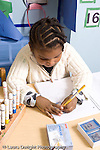 Educaton preschool 4-5 year olds girl sitting at table writing with pencil using stencil to write letters vertical