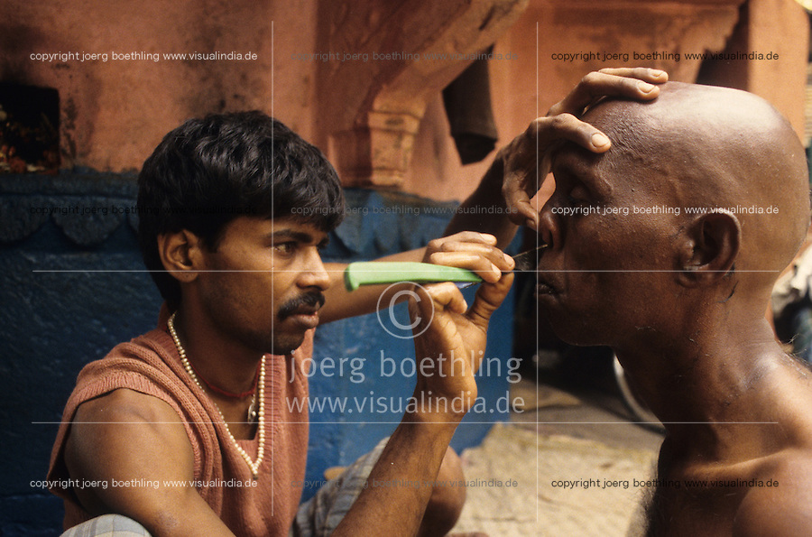 India Varanasi, ritual headshaving before cremation of dead body at Manikarnika ghat at river Ganga , is part of ritual moksha, hindu belief to get salvation of rebirth here / INDIEN Benares Varanasi Kashi, rituelle Kopfrasur vor Kremation eines Angehoerigen am Manikarnika Ghat am fuer Hindu heiligen Fluss Ganges , Hindus glauben an Ritual Moksha wer hier verbrannt wird entgeht dem Kreislauf der Wiedergeburt und kommt in den Himmel