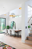 Pendant lights hang from a double height ceiling above a dining table and chairs for eight. The spacious room has a wooden floor and a glass door leading to the garden.