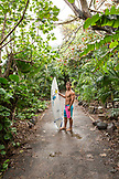 USA, Oahu, Hawaii, portrait of MMA Mixed Martial Arts Ultimate fighter Lowen Tynanes stands with his surfboard on the path parallel to Pipeline Beach North Shore of Oahu