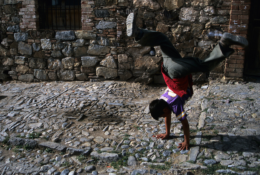 A young boy performs a cartwheel on the streets of Real de Catorce, Mexico.