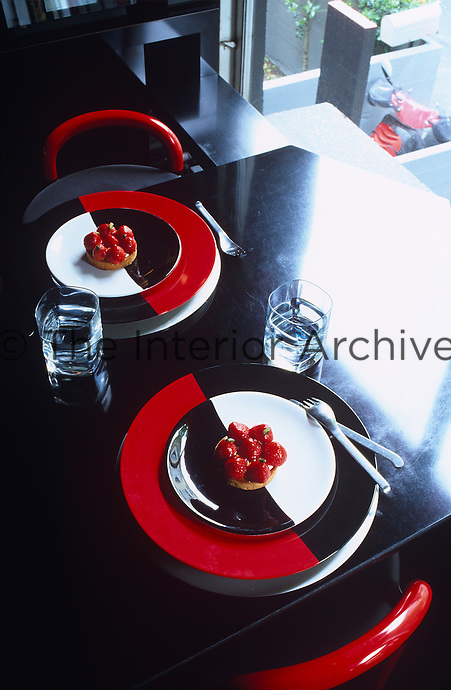 Two strawberry tarts sit on a pair of black, white and red plates on this black lacquered dining table