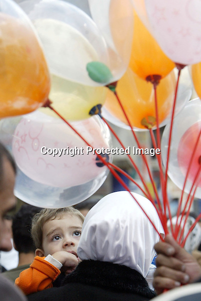 a boy looks at balloons as he is held by his mother