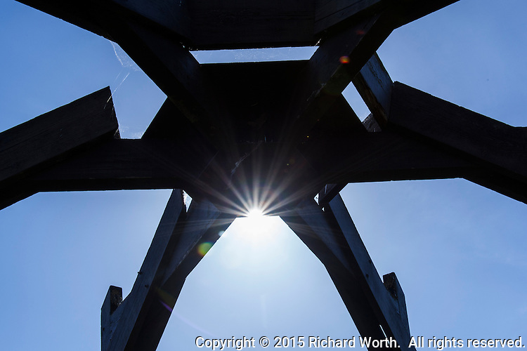 A wooden sculpture combines with a blue sky and sun burst near the playground at a neighborhood park.