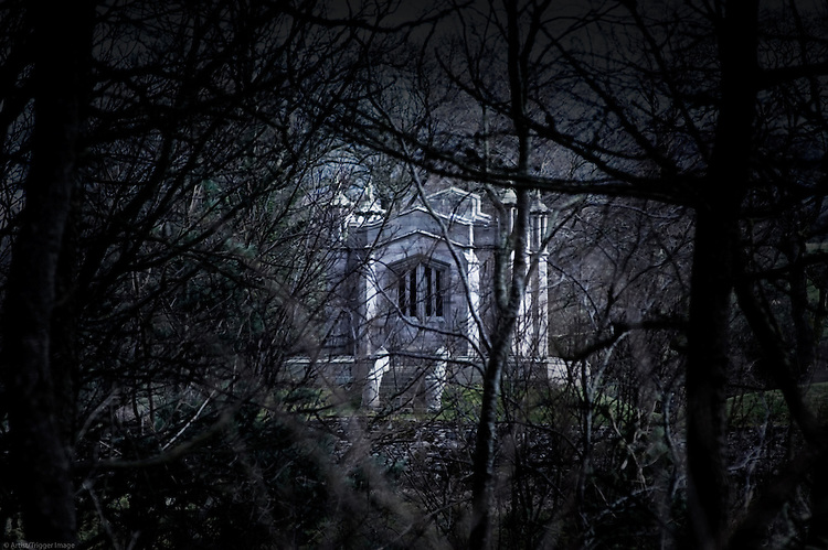 A stone mausoleum, seen through a dense forest. The Lake District, Cumbria, UK