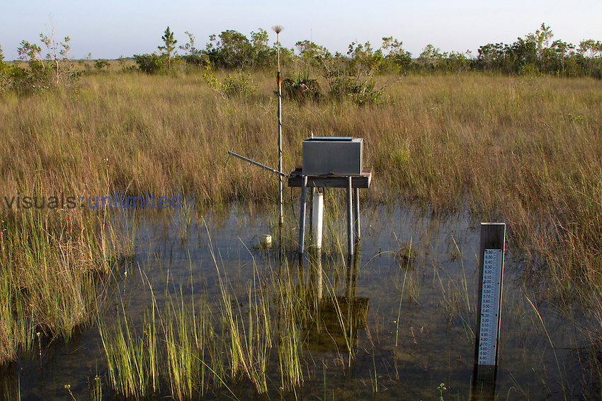 Hydrologic monitoring station in Everglades National Park which sends data about water levels and rainfall via satellite link to researchers. Shown during the wet season is the water level gauge (right) and recorder and transmitter housing over a groundwater well pipe with solar panel for power and a lightning arrester (left), Florida, USA.
