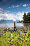 CANADA, Vancouver, British Columbia, Stepahnie Petersen walks on mossy rocks at Brigade Bay on Gambier Island, in the Howe Sound with the Britannia Range in the distance