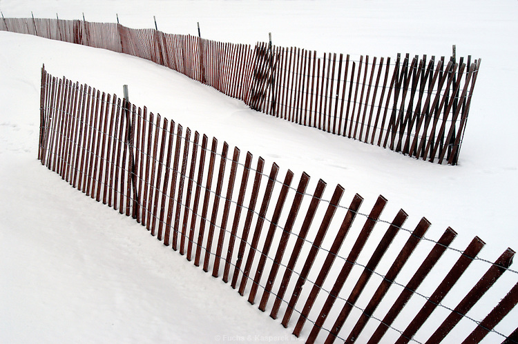Snow fences create an abstract design.