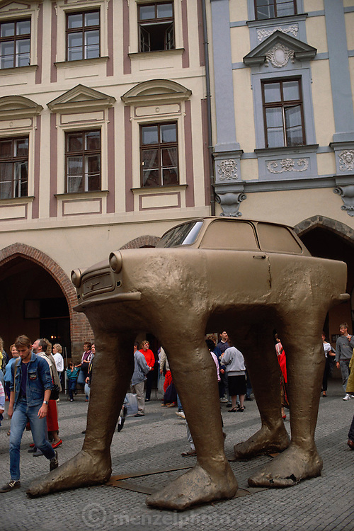 Gold painted sculpture of a Trabant (E. German made car) with legs. Prague, Czech Republic.