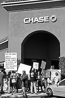 Protesters hold signs in front of a Chase bank in Irvine, CA during the Occupy Orange County, Irvine march on Saturday November 5.