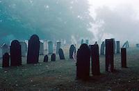 gravestones and fog in a rural graveyard, eerie scene, headstones, mist. New Hampshire.