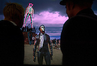 A silver-painted and masked man takes in the evening light in front of the soon the be burning effigy of man at the annual Burning Man Festival in northwestern Nevada's Conservation area. For the week of Burning Man, the counter-culture happening in the Black Rock Playa becomes one of Nevada's largest cities, attracting as many as 26,000 revelers who come to make art in the desert.