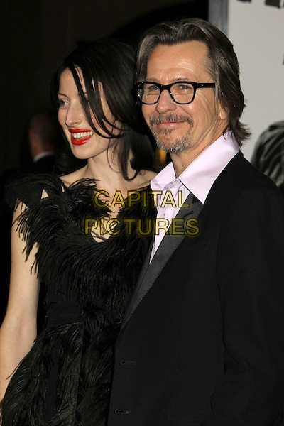 """ALEX EDENBOROUGH & GARY OLDMAN.""""The Book Of Eli"""" Los Angeles Premiere held at Grauman's Chinese Theatre, Hollywood, California, USA..January 11th, 2009.half length feather feathers dress couple black glasses pink purple shirt goatee facial hair suit jacket red lipstick .CAP/ADM/MJ.©Michael Jade/AdMedia/Capital Pictures."""