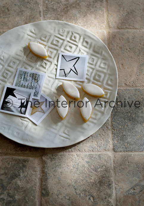 Lozenge-shaped biscuits and a selection of small cards adorn a simple white plate placed on the tiled floor of the kitchen