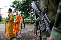 Buddhist monks at 6 in the morningin the streets of Pattani collecting the alms. Because of their morning rutine, the monks has become a favourite target for the islamic militants. Bombing and beheadings of monks has becommen more frequent. The army now escorts the monks whereever they go to enshure their security. Thailand is struggling to keep up appearances as the land of smiles has to face up to its troubled south. Since 2004 more than 3500 people have been killed and 4000 wounded in a war we never hear about. In the early hours of January 4th 2004 more than 50 armed men stormed a army weapons depot in Narathiwat taking assault rifles, machine guns, rocket launchers, pistols, rocket-propelled grenades and other ammunition. Arsonists simultaneously attacked 20 schools and three police posts elsewhere in Narathiwat. The raid marked the start of the deadliest period of armed conflict in the century-long insurgency. Despite some 30,000 Thai troops being deployed in the region, the shootings, grenade attacks and car bombings happen almost daily, with 90 per cent of those killed being civilians. 26.09.07. Photo: Christopher Olssøn.