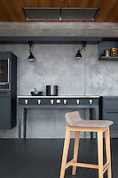 The black melamine kitchen features contemporary furniture and a black-tiled floor
