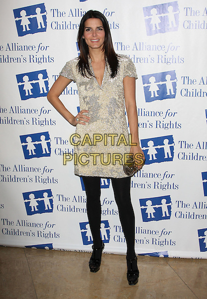 ANGIE HARMON.Attending The Alliance for Children's Rights held At The Beverly Hilton Hotel, Beverly Hills, California, USA,.10th February 2010..full length gold silver dress black tights shoes platform clutch bag hand on hip .CAP/ADM/KB. ©Kevan Brooks/AdMedia/Capital Pictures..
