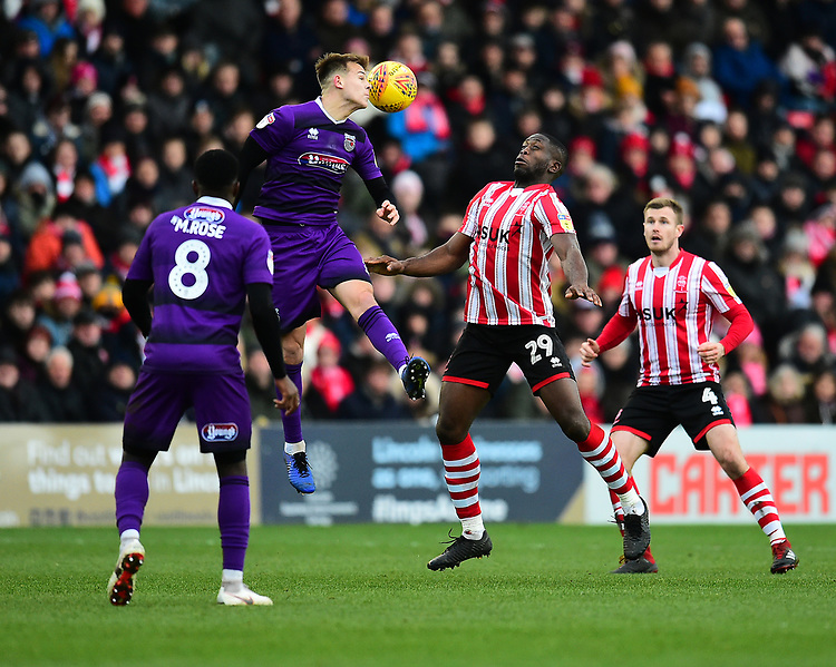 Grimsby Town's Jake Hessenthaler clears under pressure from Lincoln City's John Akinde<br /> <br /> Photographer Andrew Vaughan/CameraSport<br /> <br /> The EFL Sky Bet League Two - Lincoln City v Grimsby Town - Saturday 19 January 2019 - Sincil Bank - Lincoln<br /> <br /> World Copyright &copy; 2019 CameraSport. All rights reserved. 43 Linden Ave. Countesthorpe. Leicester. England. LE8 5PG - Tel: +44 (0) 116 277 4147 - admin@camerasport.com - www.camerasport.com