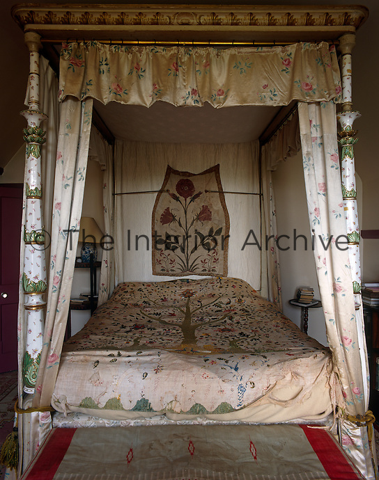 A ceramic four-poster bed with satin curtains and antique textiles