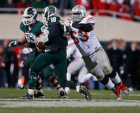 Ohio State Buckeyes defensive tackle Michael Bennett (63) sacks Michigan State Spartans quarterback Connor Cook (18) during the third quarter of the NCAA football game at Spartan Stadium in East Lansing, Michigan on Nov. 8, 2014. (Adam Cairns / The Columbus Dispatch)