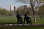 Two mothers walking with baby strollers in City Park, Denver, Colorado, USA .  John offers private photo tours in Denver, Boulder and throughout Colorado. Year-round Colorado photo tours.