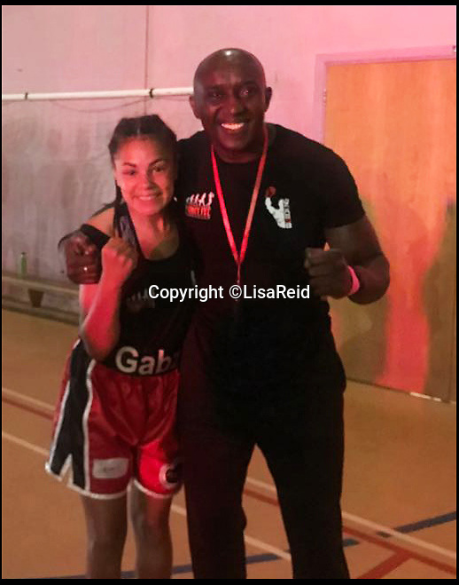 BNPS.co.uk (01202 558833)Pic: LisaReid/BNPS<br /> <br /> Gabrielle Reid with trainer Mo Kargbo after winning her first bout.<br /> <br /> An inspiring 14 year old girl with cerebral palsy who was once wheelchair bound has taken part in her boxing match - and she won.Gabrielle Reid was born with right hemiplegia which affects her muscle control and movement making it difficult to walk, let alone spar in the ring.However, since taking up boxing five years ago, her movement and coordination have improved to such an extent that she has just competed in her first bout in her home town of Poole, Dorset.She defeated a fully able bodied fighter in a three round contest and has now set her sights on her second bout, scheduled for October.